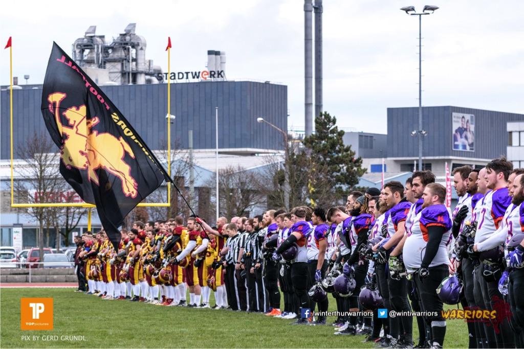 Die Mannschaften bei der Nationalhymne, beim American Football NLA Spiel zwischen den Winterthur Warriors und den Gladiators beider Basel, am Samstag, den 31. Maerz 2018 im Stadion Deutweg in Winterthur. (Foto: BEAUTIFUL SPORTS / Gerd Gruendl)Bild-Id: GRG_180331-0954